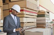 Stock Photo of African American male contractor using tablet PC with stacked wooden planks in