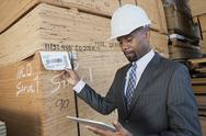 Stock Photo of African American male contractor using tablet PC while inspecting wooden planks