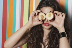 Stock Photo of Young woman covering her eyes with peach against striped background
