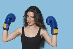 Portrait of a beautiful young female boxer raising arms in victory against blue - stock photo