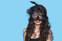 Portrait of a young woman wearing exotic eye mask over blue background Stock Photos