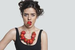 Portrait of a young woman wearing strawberry necklace while biting one piece - stock photo