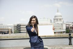 Indian businesswoman gesturing thumbs up as she holds a sign with St. Paul's Stock Photos