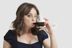 Stock Photo of Portrait of beautiful young woman drinking wine against gray background
