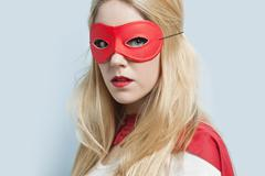 Portrait of a blond young woman wearing red eye mask against light blue Stock Photos