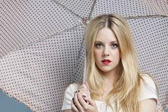 Close-up portrait of young woman holding polka dots umbrella - stock photo