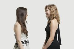 Stock Photo of Two female friends looking at each other and smiling over gray background