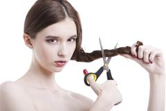 Portrait of beautiful young woman with scissors cutting her hair over white Stock Photos