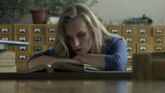 Girl student reading books in the library Stock Footage