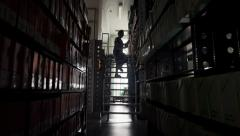 Woman librarian selects the book from a high shelf - stock footage