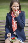 Stock Photo of Portrait of a young businesswoman eating salad while sitting on bench at park