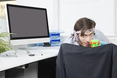 Portrait of young businessman aiming with toy gun at desk Stock Photos