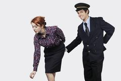 Portrait of young pilot touching flight attendant inappropriately against gray Stock Photos