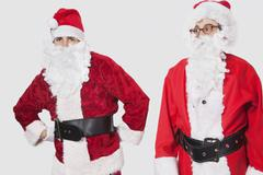Young men in Santa costume standing against gray background Stock Photos