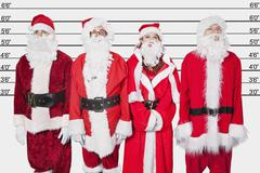 People in Santa costume standing side by side against police lineup - stock photo