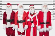 Stock Photo of People in Santa costume standing side by side against police lineup