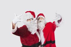 Portrait of young men in Santa costume gesturing over gray background Stock Photos