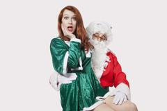 Portrait of Santa touching woman inappropriately against gray background - stock photo
