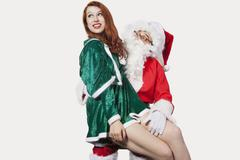 Happy young woman sitting on Santa's laps against gray background - stock photo