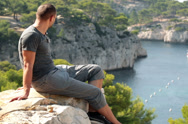 Stock Video Footage of Young man relaxing on cliff in beautiful nature scenery NTSC