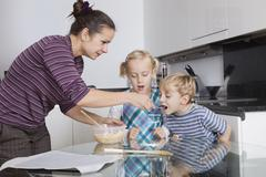 Mother with children baking and tasting cookie batter in kitchen Stock Photos