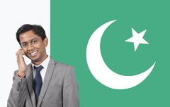 Portrait of young businessman using cell phone over Pakistani flag - stock photo