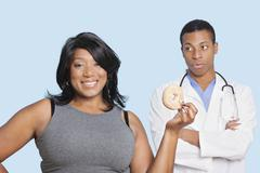Overweight mixed race woman with donut by doctor over blue background - stock photo