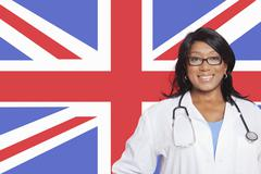 Portrait of confident mixed race female surgeon over British flag Stock Photos
