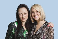 Portrait of two beautiful young women smiling over blue background Stock Photos