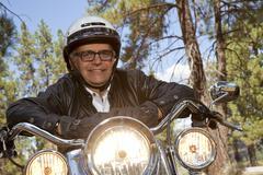 Senior man wearing helmet leaning on motorcycle handlebars in forest Stock Photos
