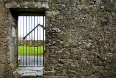 Locked gate in old stone wall Stock Photos