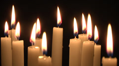 Group of candles burning on black background. Stock Footage