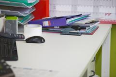 Close-up of real life messy desk in  office Stock Photos