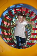 Young girl climbs through netted tunnel in soft play centre Stock Photos