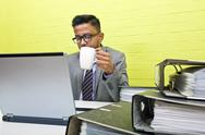 Stock Photo of Portrait of Indian Businessman holding mug and working on his laptop computer at