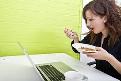Close up of woman eating at her desk Stock Photos