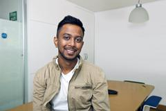 Stock Photo of Young Indian man smiling at camera in his office
