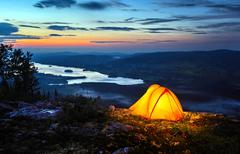.a tent lit up at dusk - stock photo