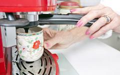 Cropped image of woman dispensing coffee from machine in kitchen - stock photo