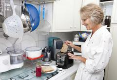 Stock Photo of Happy senior woman preparing toast in domestic kitchen