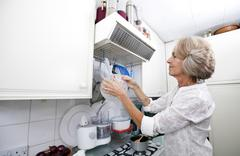 Stock Photo of Senior woman hanging colander in domestic kitchen