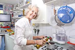Portrait of senior woman pouring olive oil to saucepan in domestic kitchen Stock Photos