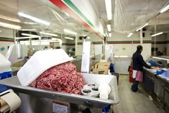 Minced meat in container with employee standing in background at store Stock Photos