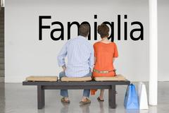 """Rear view of couple seated on bench reading Italian text """"Famiglia"""" (family) on - stock photo"""