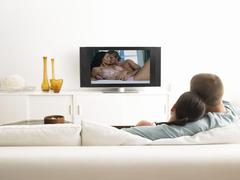 Back view of affectionate couple on sofa watching television - stock photo