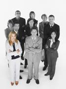 Portrait of confident business team standing with arms crossed against white - stock photo