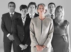 Ambitious businesswoman with team of professionals against gray background - stock photo