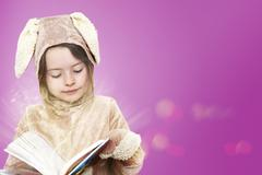 Little girl dressed as a bunny rabbit reading a book - stock photo