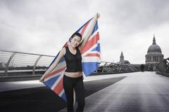Olympic competitor with Union Jack in front of St Paul's Cathedral in London - stock photo