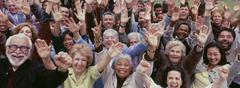 Large group of multi-ethnic people cheering with arms raised Stock Photos